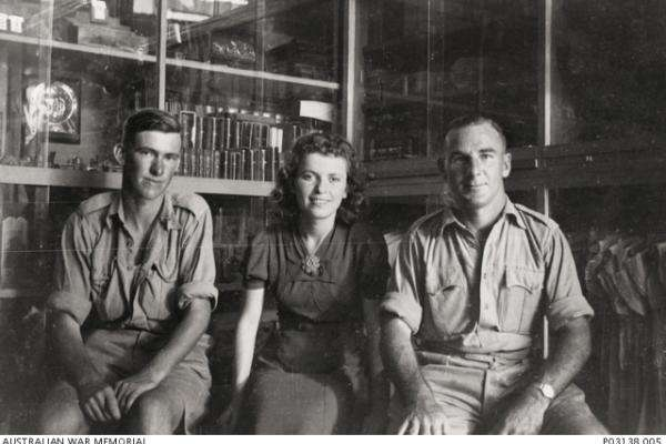 Informal portrait of VX4796 Private (Pte) Eric Clifton Eldridge, Headquarters, 17th Brigade, Australian Infantry, of Horsham, Vic (left); a shop girl (centre); and VX1113 Corporal (Cpl) Henry James Bailey Spencer (enlisted as Henry Bailey Spencer), 2/7th Battalion, of Alphington, Vic (right) inside a shop selling curios and childrens' clothes in Tel Aviv.