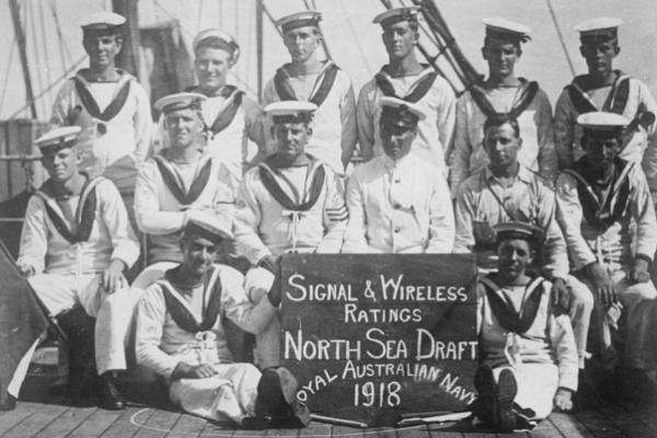 "Sailors sit behind a sign that reads ""Signal & Wireless Ratings North Sea Draft, Royal Australian Navy, 1918"