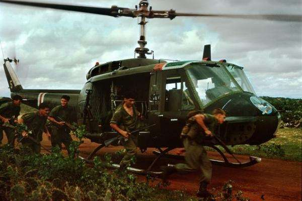 Soldiers stand by a helicopter in Vietnam