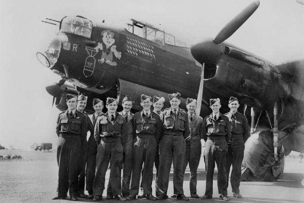 Pilots stand in front of a plane
