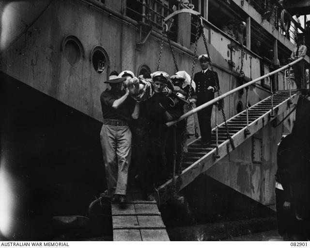 Commodore Collins, injured in the attack on HMAS Australia, is carried from an American merchant ship to a waiting ambulance.