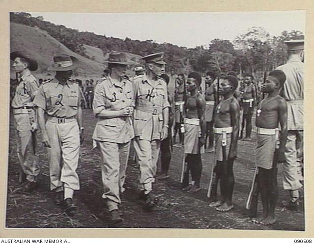 Near Nadzab, New Guinea, March 1945. Lady Wakehurst (3), accompanied by Lieutenant General V.A.H Sturdee (4), inspecting C Company, 2 New Guinea Infantry Battalion at Camp Diddy. Identified personnel are: Sergeant Don Collins (1) and Major W.L. Darcey, Brigade Major, Pacific Islands Regiment (2).