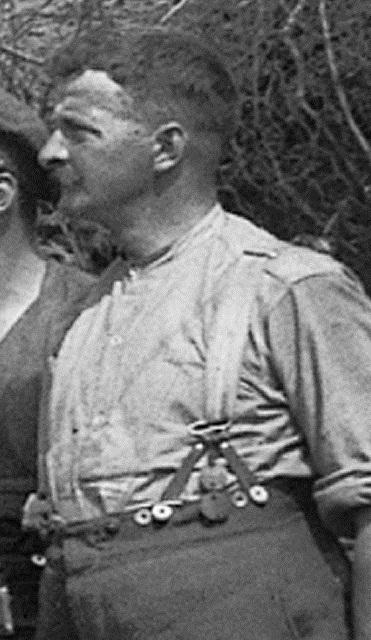 An artilleryman in his shirt and breeches wears his two identity discs hanging from his suspenders.