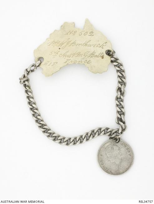 Identity bracelet  worn by Wilfred James Borthwick. The metal disc is carved in the shape of the map of Australia and has the soldier's details engraved on it. It is attached to a chain, which has an Indian coin hanging off it.