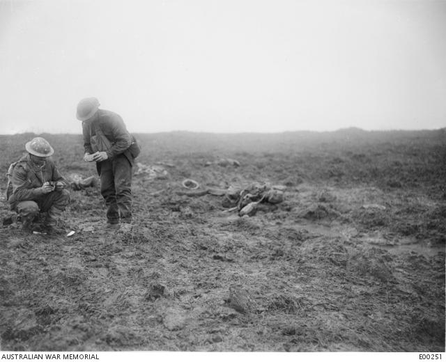 Two soldiers in a muddy landscape looking at objects collected from the battlefield.