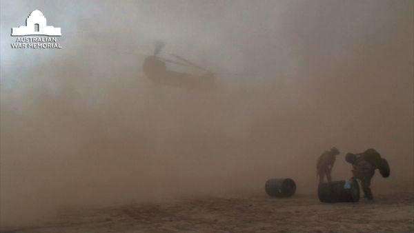 A United States Army Chinook helicopter lifting off and raising dust storm in the process