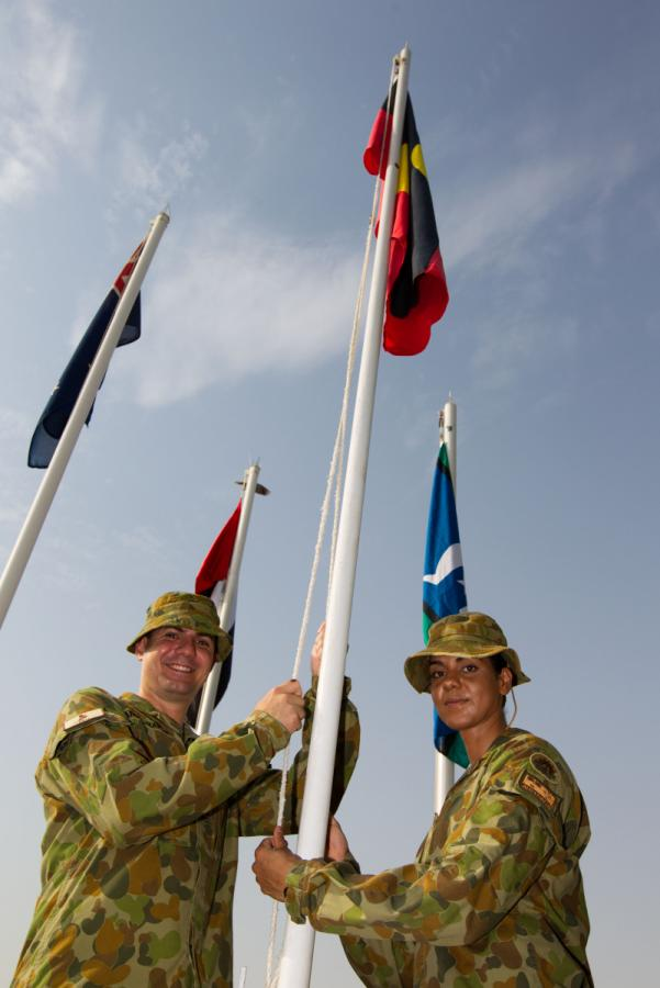 Sergeant John Angel-Hands and Lance Corporal Natalie Whyte raise the Aboriginal and Torres Strait Islander flags at Al-Minhad air base, United Arab Emirates, July 2013 courtesy Commonwealth of Australia, Department of Defence Joel Graham